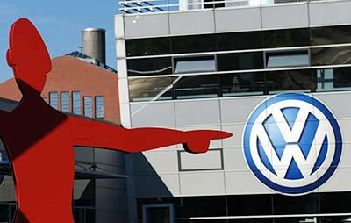"""(FILES) This picture taken on September 28, 2015 shows the logo of German car maker Volkswagen (VW) is seen at the entrance to a VW branch in Duesseldorf, western Germany.  Michael Horn, president and chief executive of Volkswagen Group of America, apologized to Congress and said the company takes """"full responsibility"""" for the emissions cheating scandal, according to testimony released on October 8, 2015.  AFP PHOTO / PATRIK STOLLARZ."""