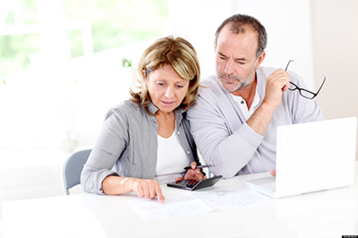 Couple reading construction plan at home with use of laptop; Shutterstock ID 104521904; PO: aol; Job: production; Client: drone