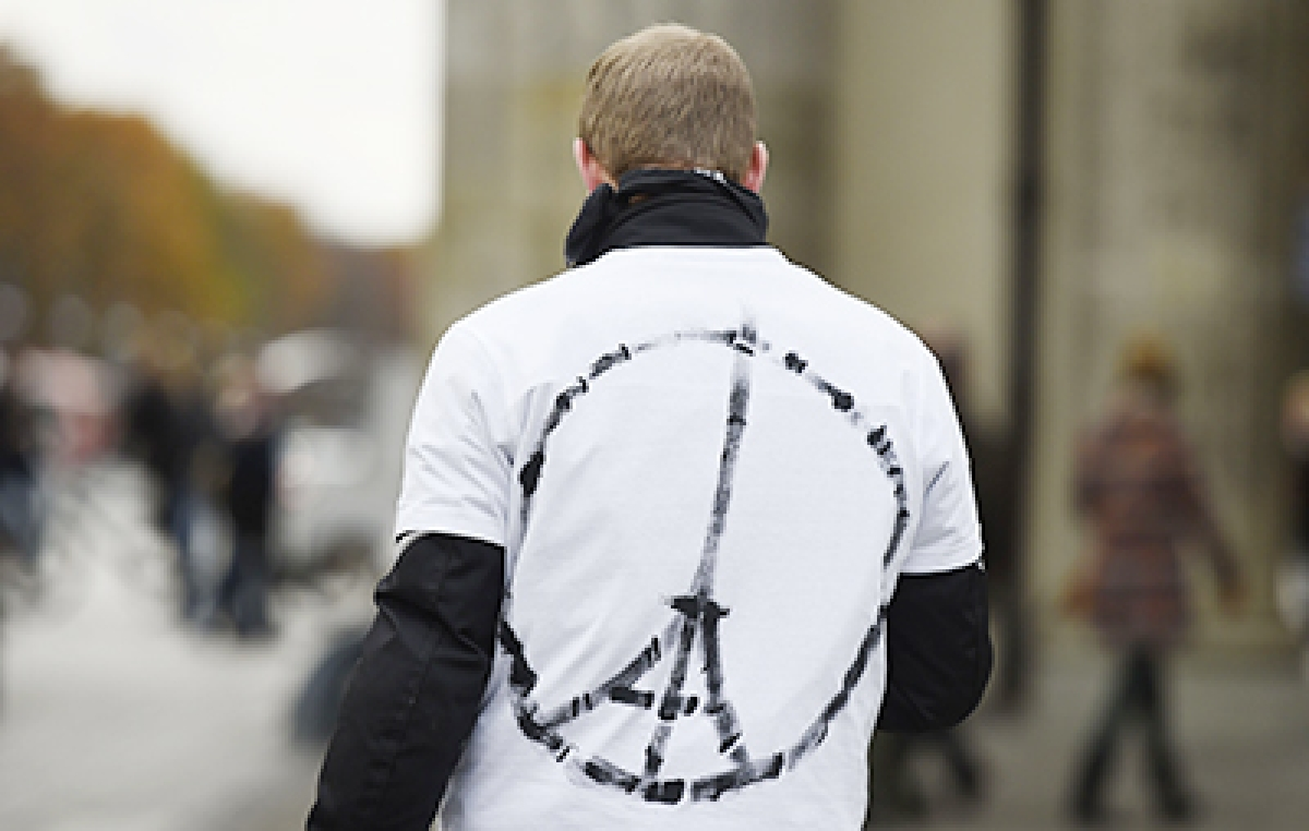 A man wears a shirt with a sign combining a peace symbol with the Eiffel tower near the French embassy in Berlin on November 14, 2015, a day after deadly attacks in Paris. The string of coordinated attacks in and around Paris late November 13, 2015 left more than 120 people dead, in the worst such violence in France's history.  AFP PHOTO / TOBIAS SCHWARZ