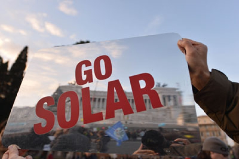"A man holds a placard reading ""Go Solar"" during a rally calling for action on climate change on November 29, 2015 in Rome a day before the launch of the COP21 conference in Paris. Some 150 leaders including US President Barack Obama, China's Xi Jinping, India's Narendra Modi and Russia's Vladimir Putin will attend the start of the UN conference Monday, tasked with reaching the first truly universal climate pact. The goal is to limit average global warming to two degrees Celsius (3.6 degrees Fahrenheit), perhaps less, over pre-Industrial Revolution levels by curbing fossil fuel emissions blamed for climate change.  AFP PHOTO / TIZIANA FABI"