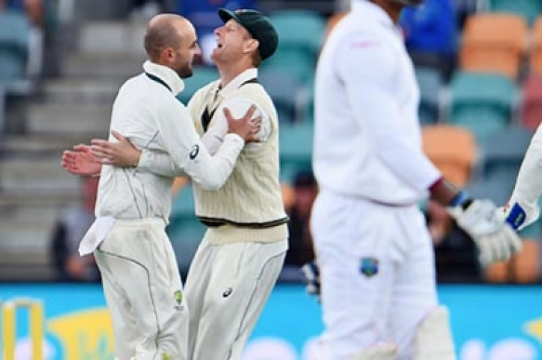 Australian spinner Nathan Lyon (L) celebrates with teammate Adam Voges (C) after dismissing West Indies batsman Marlon Samuels (R) on the second day of the first cricket Test match in Hobart on December 11, 2015.   AFP PHOTO / William WEST   --IMAGE RESTRICTED TO EDITORIAL USE - NO COMMERCIAL USE--