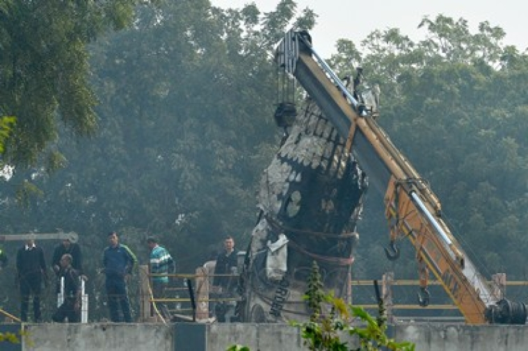 A piece of plane wreckage is hoisted by a crane as rescue personel look on at the crash site of a chartered army plane close to the main airport in New Delhi on December 22, 2015.     A chartered Indian aircraft carrying military personnel exploded in a fireball and killed all 10 people on board after crashing near New Delhi's main airport, a minister said.   AFP PHOTO/  CHANDAN KHANNA