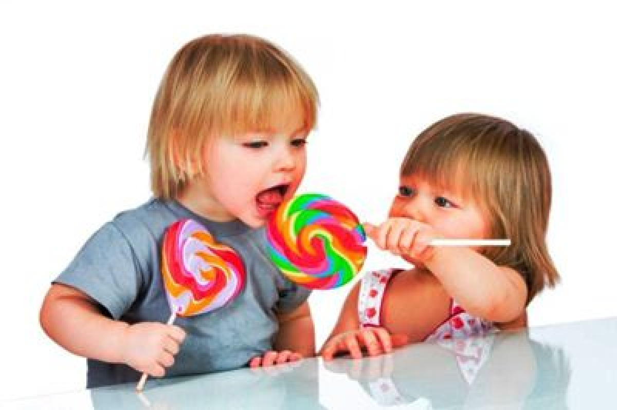 Babies eating a sticky lollipop