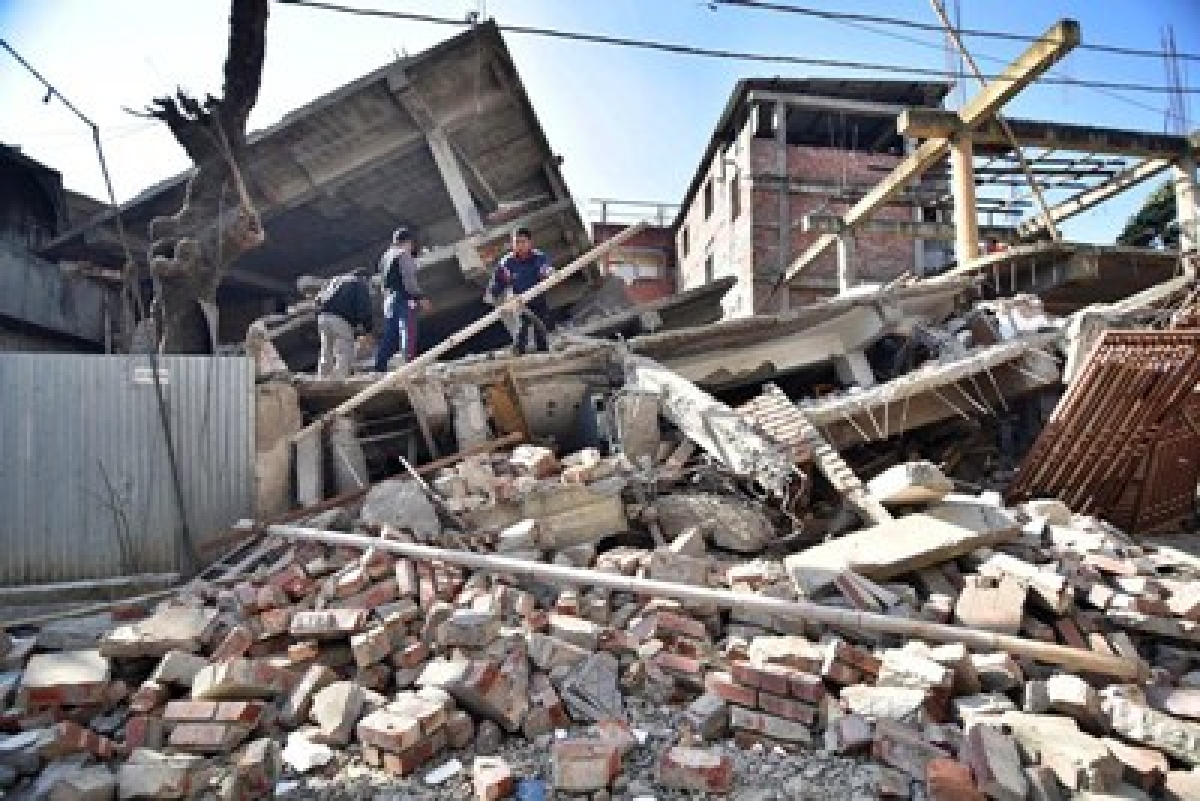Indian men search through the debris of a collapsed building following a 6.7 magnitude earthquake, in Imphal on December 4, 2015.  At least eight people were killed and scores injured January 4, when a strong 6.7 magnitude earthquake struck northeast India, sending panicked residents fleeing into the streets even hundreds of kilometres away in Bangladesh.   AFP PHOTO/ BIJU BORO