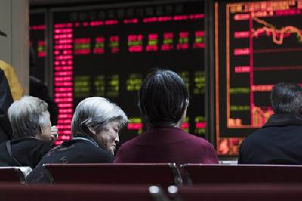 Investors look at screens showing stock market movements at a securities company in Beijing on January 13, 2016. Shanghai stocks gave up early gains on January 13 to end the morning flat despite a better-than-expected trade report out of China, but Hong Kong rallied/ File