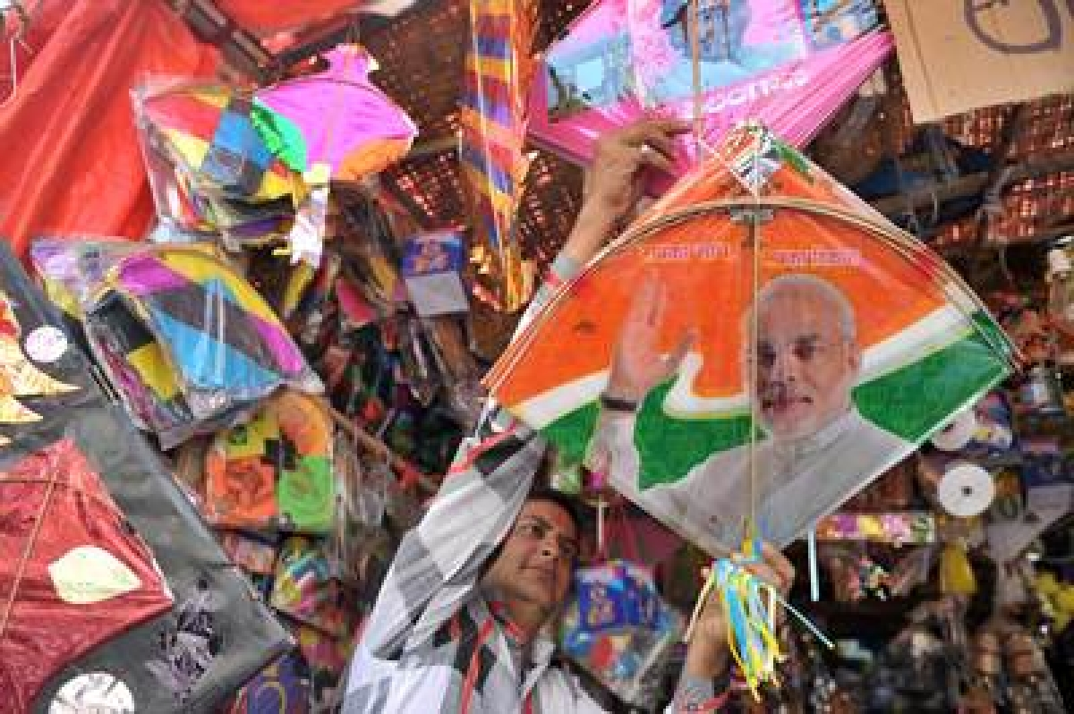 An Indian vendor displays kites printed with the portrait of Prime Minister Narendra Modi ahead of the forthcoming Makar Sankranti kite festival in Indore on January 12, 2016. The Makar Sankranti festival, which will be celebrated on January 14 this year, celebrates the beginning of the harvest season.    AFP PHOTO/ Noah SEELAM