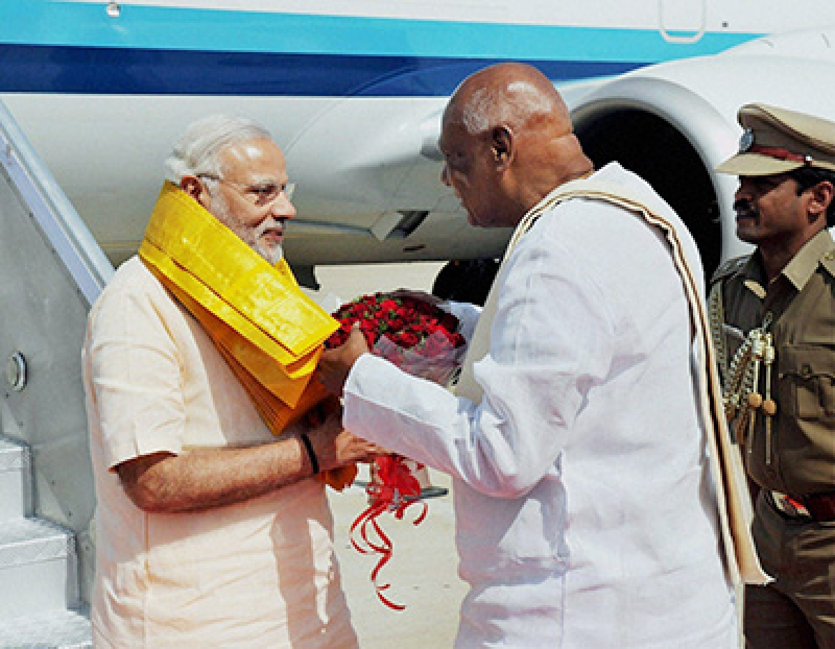 Coimbatore: Prime Minister Narendra Modi being welcomed by the Governor of Tamil Nadu K Rosaiah, on his arrival, at Coimbatore on Tuesday. PTI Photo(PTI2_2_2016_000063B)