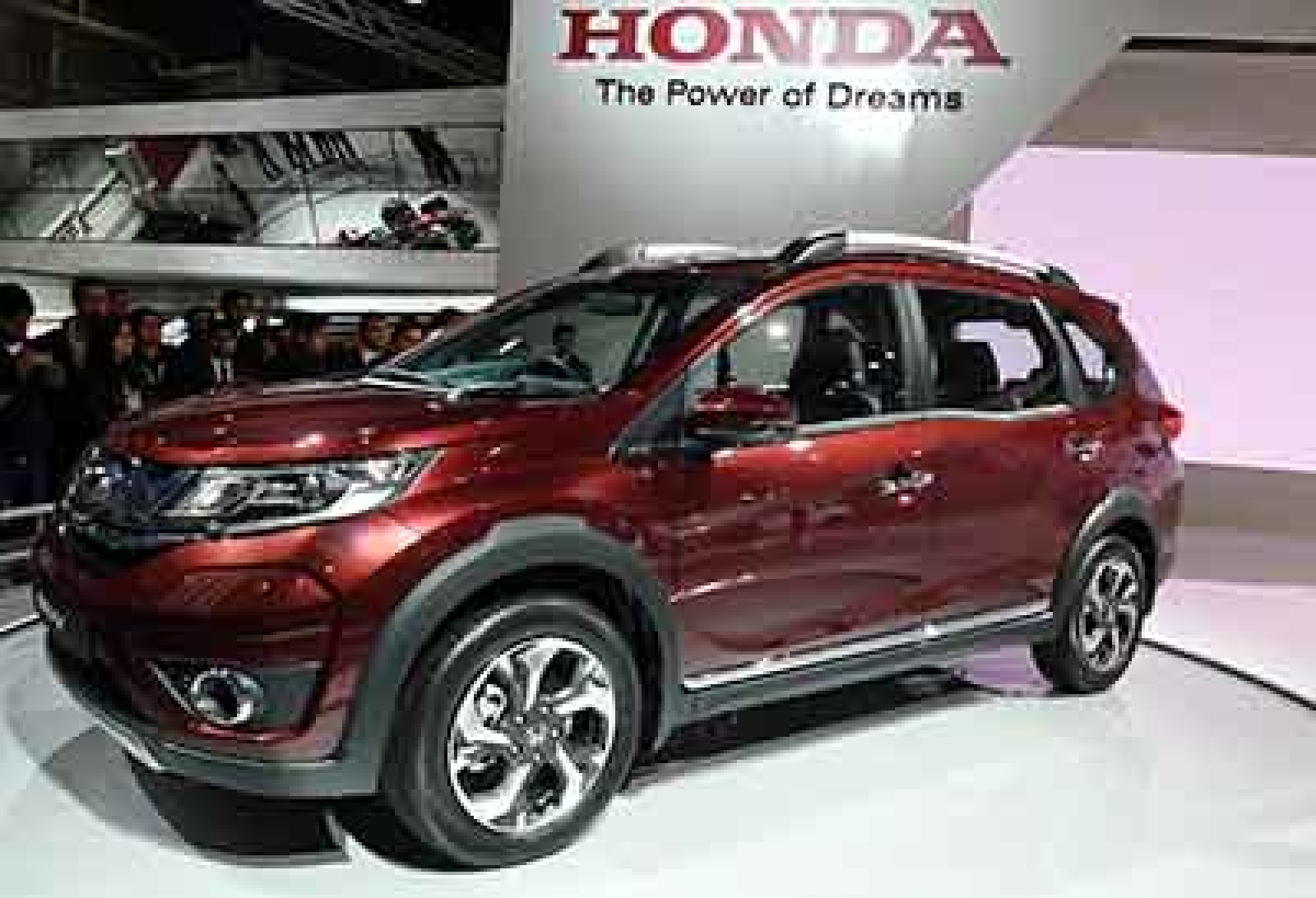 """Visitors look at Honda's """"BR-V"""" SUV at Auto Expo 2016 in Greater Noida some 45kms east of New Delhi on February 4, 2016. India's flagship auto show opened its doors in New Delhi with a new batch of diesel-guzzling SUVs on proud display, despite industry uncertainty about a pollution crackdown targeting motorists in the capital. More than 80 vehicle launches were expected at the Auto Expo 2016, the biggest edition in the show's 30-year history, with the Fiat Chrysler-owned Jeep making its India debut and hoping to capitalise on the popularity of sports utility vehicles. . AFP PHOTO / Prakash SINGH"""