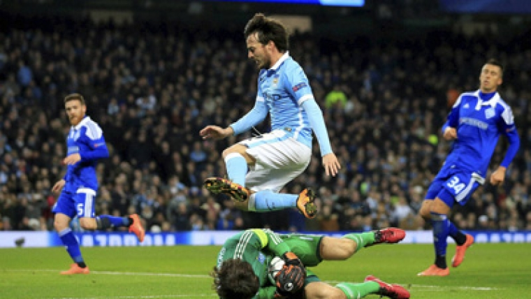 Manchester City's David Silva leaps over the diving Kiev's goalkeeper Oleksandr Shovkovskiy during the  match between Manchester City and Dynamo Kiev