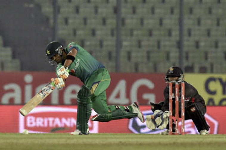 Pakistan cricketer  Umar Akmal (L) plays a shot as the United Arab Emirates wicketkeeper Swapnil Patil (R) looks on during the Asia Cup T20 cricket tournament match between Pakistan and United Arab Emirates at the Sher-e-Bangla National Cricket Stadium in Dhaka