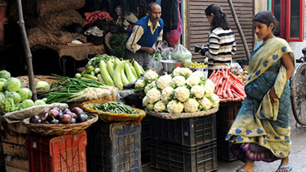 An Indian customer purchase vegetables from a shop at a market
