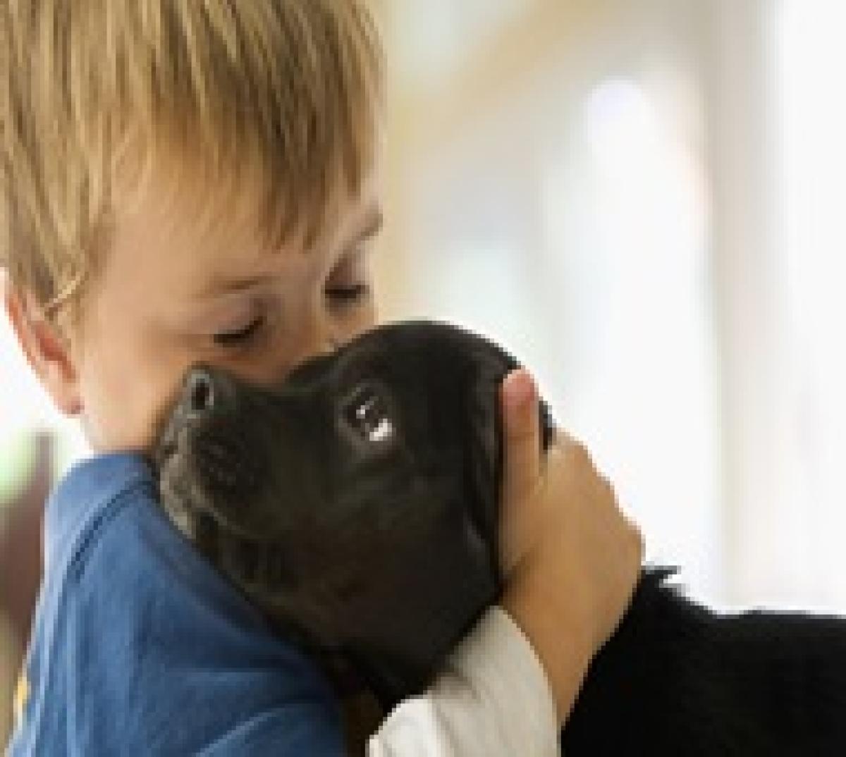 Boy (3-4) hugging puppy, eyes, closed
