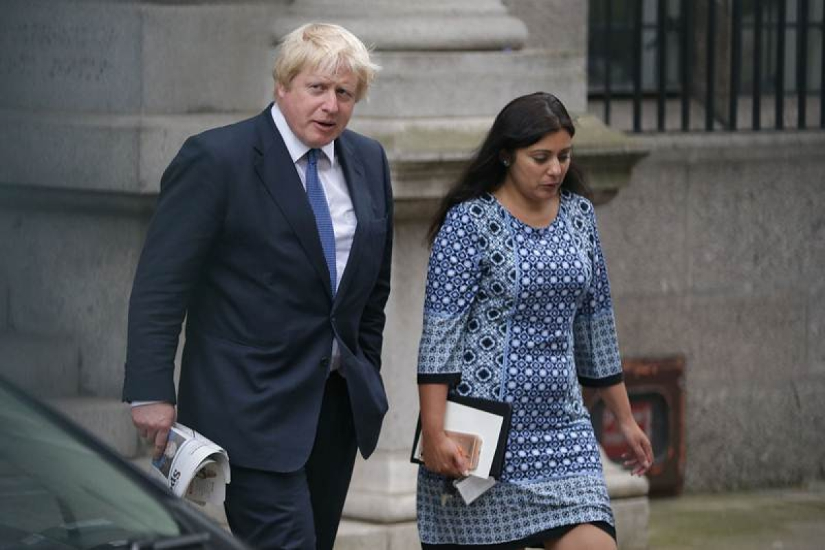 Former London mayor and Brexit campaigner Boris Johnson (L) walks across a carpark by the Houses of Parliament and Portcullis House in central London on June 28, 2016. Popular British MP Boris Johnson is one step away from his dream of becoming Prime Minister, but the shadow of the ill-tempered EU referendum campaign looms large over his leadership bid. / AFP PHOTO / DANIEL LEAL-OLIVAS