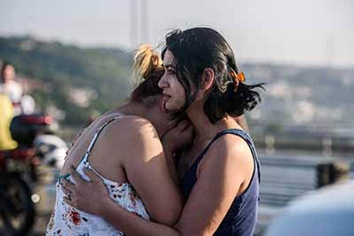 Women react after people took over military position on the Bosphorus bridge in Istanbul on July 16, 2016. The number of dead from a coup attempt in Turkey has risen to 90, the state-run news agency Anadolu reported on July 16, 2016, adding that 1,154 people were wounded. Nearly 200 unarmed soldiers at the Turkish military headquarters have meanwhile surrendered, an official said, adding that special troops were currently securing the complex. / AFP PHOTO / OZAN KOSE