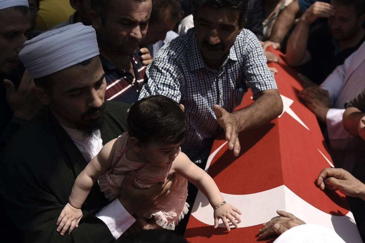 """A man holds a baby girl near the flag-draped coffin of a relative as he mourns in Istanbul on July 17, 2016, during the funeral of seven victims of the July 15 coup attempt.  Turkish President Recep Tayyip Erdogan vowed on July 17 to purge the """"virus"""" within state bodies, during a speech at the funeral of victims killed during the coup bid he blames on his enemy Fethullah Gulen. / AFP PHOTO / ARIS MESSINIS"""