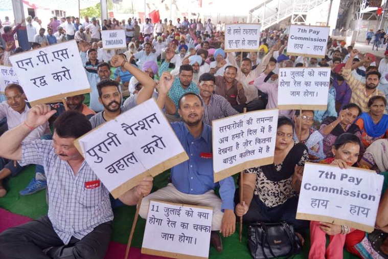 Indian railway employees, along with members of Northern Railway Men's Union (NRMU), hold placards and shout slogans against the 7th Pay Commission during a demonstration at a railway station in Amritsar on June 28, 2016. Railway unions have called for a nationwide indefinite strike from July 11 in support of several long-pending demands, including review of the new pension scheme and Seventh Pay Commission recommendations. / AFP PHOTO / NARINDER NANU
