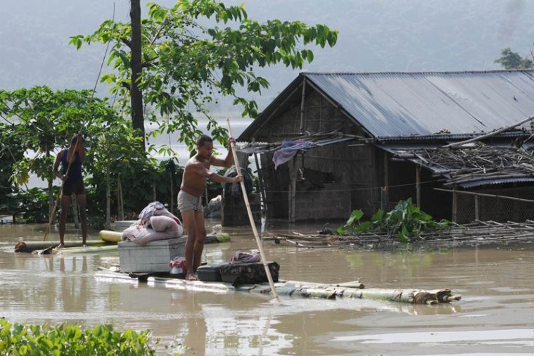 A villager takes his belonging on a banana raft at his house is half submerged in flood water at the flood affected area at Mayong village in Morigoan district, on Thursday, June 28, 2012. More than 850,000 people have been displaced and road communication disrupted in several parts of the north-eastern Indian state of Assam due to flooding, caused by seasonal monsoon rains, government official said. Photo by Biju BORO