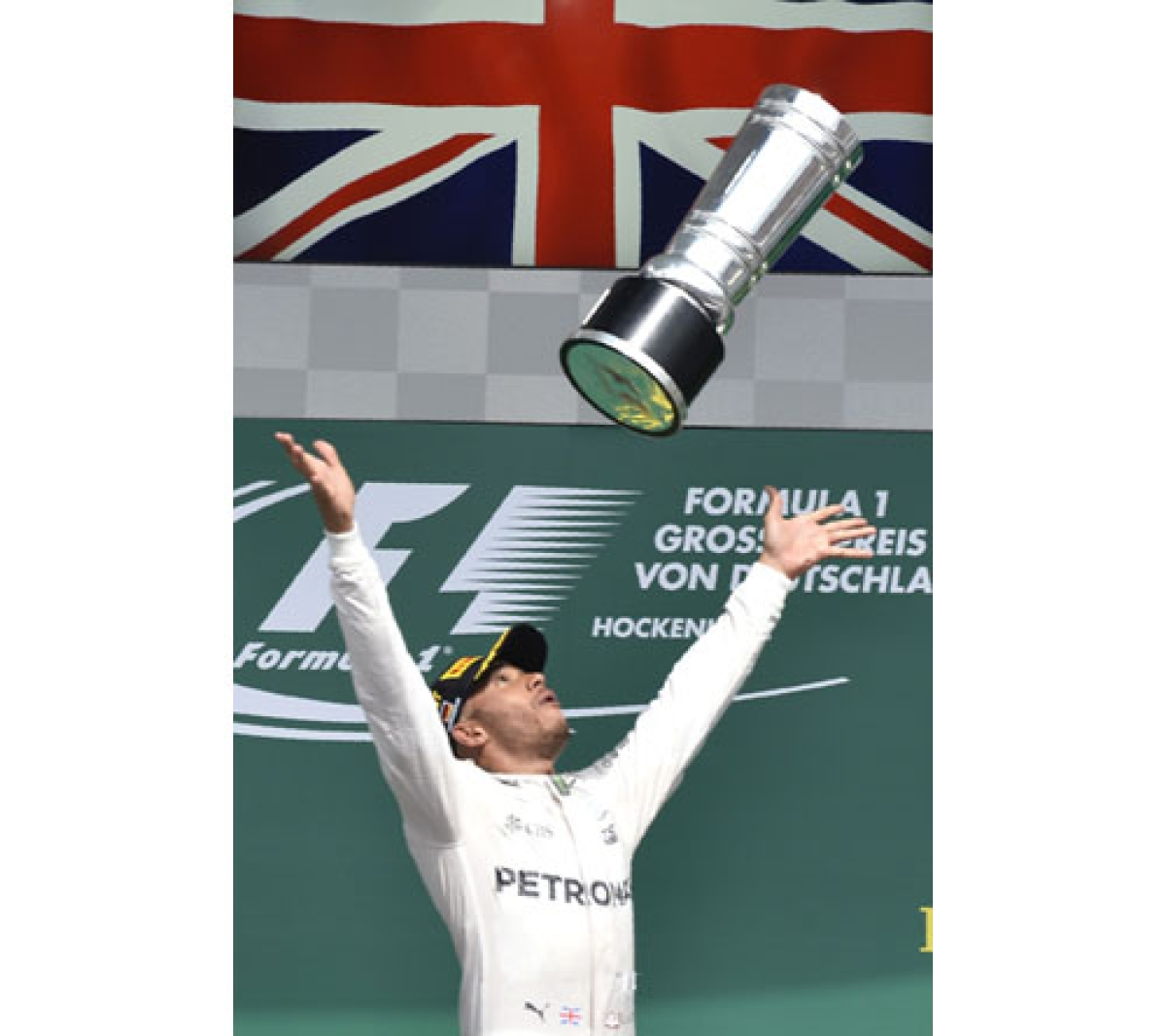 TOPSHOT - Mercedes AMG Petronas F1 Team's British driver Lewis Hamilton (C) throws the trophy after winning next to second placed Red Bull Racing's Australian driver Daniel Ricciardo (L) amd Red Bull racing's Belgian-Dutch driver Max Verstappen (R) at the Hockenheim circuit, southern Germany, on July 31, 2016 during the Formula One Grand Prix of Germany. / AFP PHOTO / Thomas Kienzle