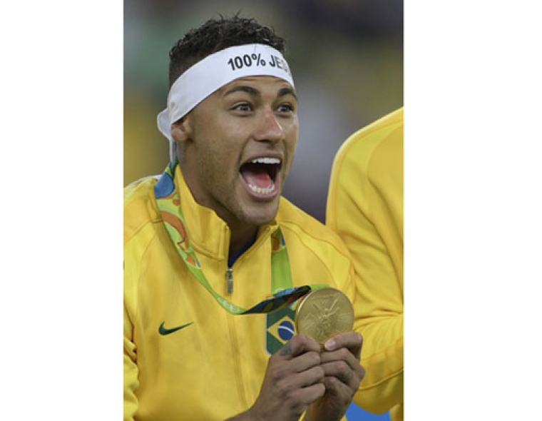 Brazil's forward Neymar celebrates on the podium during the medal presentation following the Rio 2016 Olympic Games men's football gold medal match between Brazil and Germany at the Maracana stadium in Rio de Janeiro on August 20, 2016.  Neymar struck the winning penalty as Brazil claimed a first ever Olympic football gold medal with victory over Germany at the Maracana on Saturday. / AFP PHOTO / Juan Mabromata