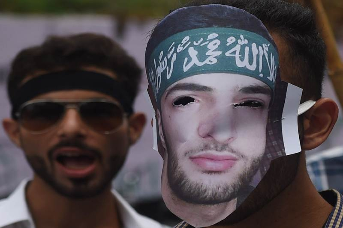 Pakistani Kashmiri students wear masks bearing the image of slain Indian Kashmiri rebel leader Burhan Wani as they shout anti-Indian slogans during at a rally to show solidarity with Indian Kashmiri Muslims in Karachi on August 15, 2016. / AFP PHOTO / RIZWAN TABASSUM