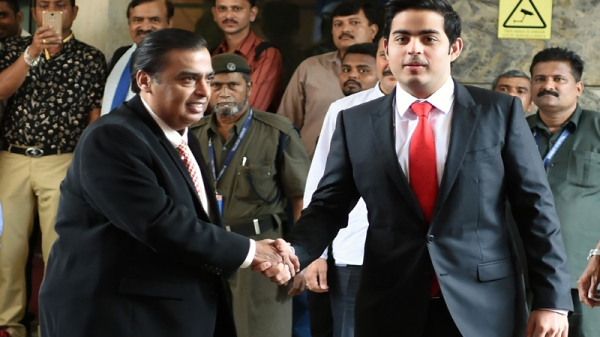 India's Reliance Industries chairman, Mukesh Ambani (L) shakes hand with his son Akash as they arrive for the company's annual general meeting in Mumbai.