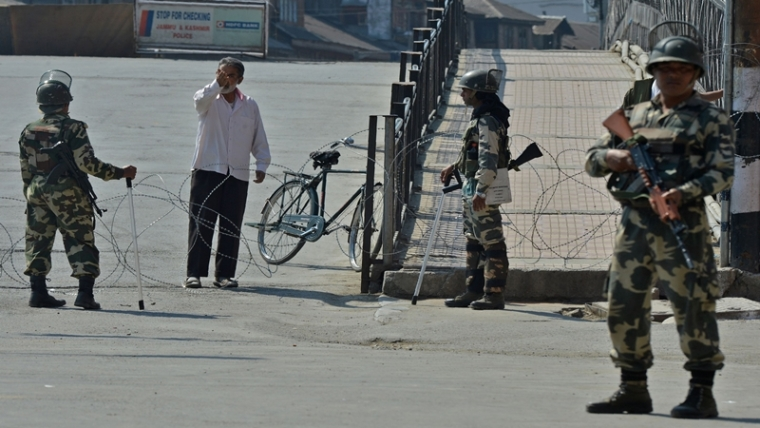 Indian paramilitary troopers stop a Kashmiri pedestrian as they stand guard during a curfew in the Lal Chowk area of central Srinagar