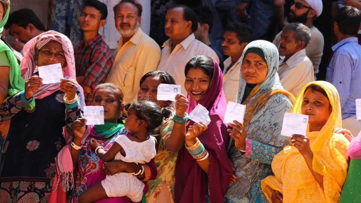 Voter standing in a queue showing  their voter slip wait for their turn to cast their vote in Jammu.