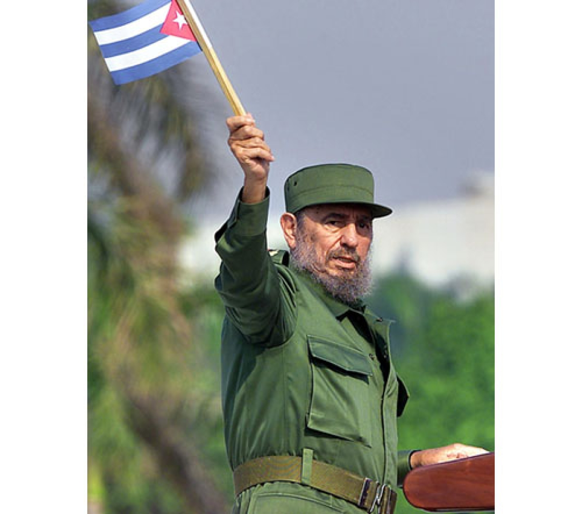 (FILES) This 01 May 2002 file photo shows Cuban President Fidel Castro waving a Cuban flag during a May Day rally in Havana. Cuban revolutionary icon Fidel Castro died late on November 25, 2016 in Havana, his brother, President Raul Castro, announced on national television. / AFP PHOTO / ADALBERTO ROQUE