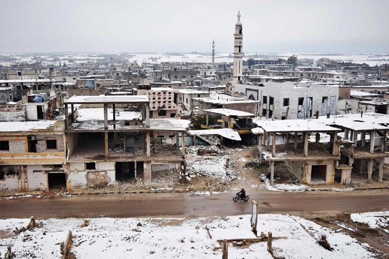 A Syrian man rides his motorbike past damaged buildings covered with snow on December 18, 2016, in a rebel-held district of Homs. / AFP PHOTO / MAHMOUD TAHA