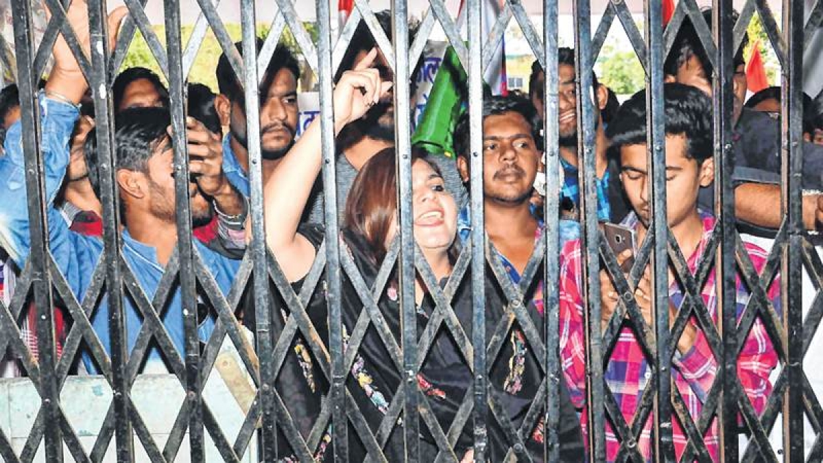 AICC member Noori Khan and local Congress party workers staging a protest after locking the entrance gate of power distribution company in Ujjain on Wednesday. FP PHOTO