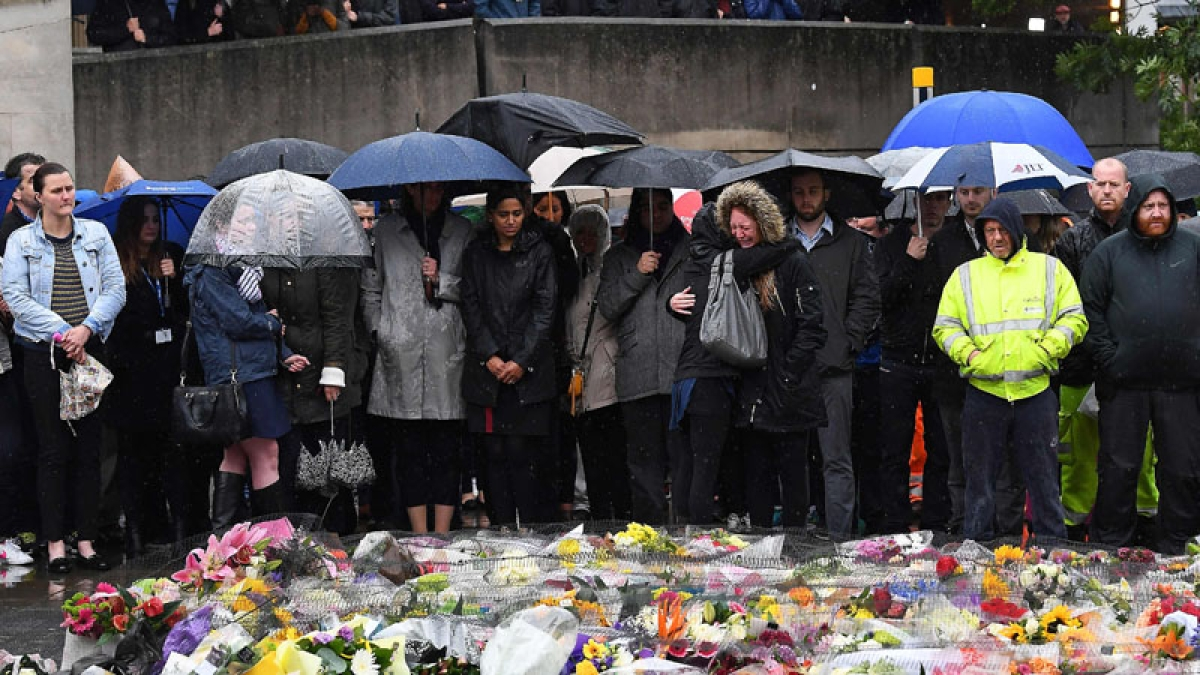 TOPSHOT - A woman reacts as people observe a minutes' silence at south-side of London Bridge in London on June 6, 2017, in memory of the victims of the June 3 terror attacks. Police on Monday identified two of the three London attackers as Khuram Butt and Rachid Redouane, after Britain's third terror assault in less than three months, as Prime Minister Theresa May came under mounting pressure over security just days ahead of elections. / AFP PHOTO / Justin TALLIS