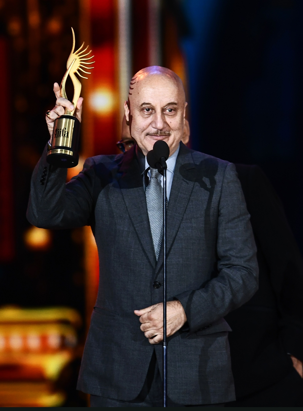 """Winner of Performance in a Supporting Role – Male, Bollywood actor Anupam Kher for """"M.S. Dhoni"""" accepts the award during 18th International Indian Film Academy (IIFA) Festival at the MetLife Stadium in East Rutherford, New Jersey, on July 15, 2017. / AFP PHOTO / JEWEL SAMAD"""