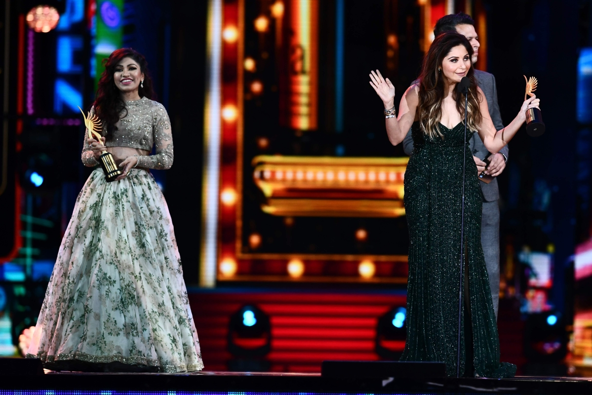 """Winners of Best Playback Singer – Female, Kanika Kapoor (R) for """"Da Da Dasse"""" from movie """"Udta Punja"""" and Tulsi Kumar (L) for """"Soch Na Sake"""" from movie """"Airlift"""" receive their awards during the 18th International Indian Film Academy (IIFA) Festival at the MetLife Stadium in East Rutherford, New Jersey, on July 15, 2017. / AFP PHOTO / JEWEL SAMAD"""