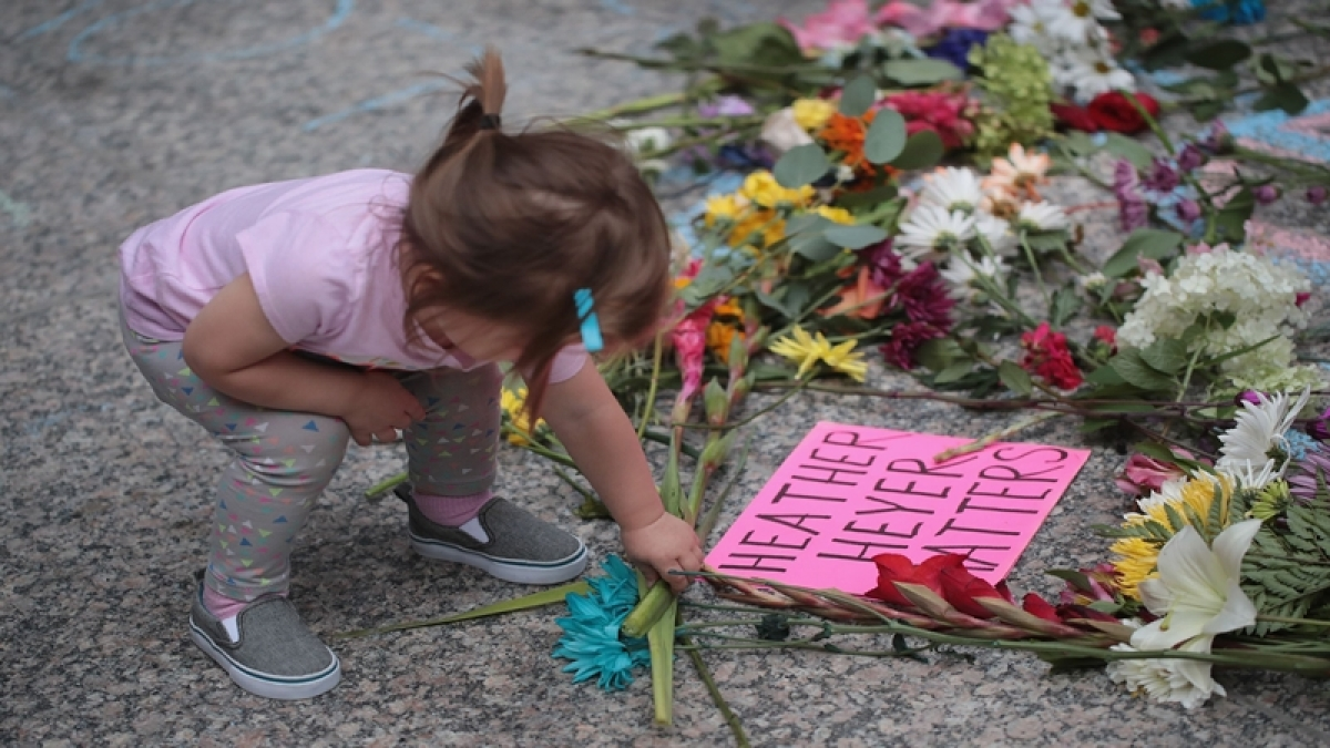 CHICAGO, IL - AUGUST 13: A young girl puts flowers on a memorial to Heather Heyer that was chalked on the pavement during a demonstration on August 13, 2017 in Chicago, Illinois. Heyer was killed and 19 others were injured yesterday in Charlottesville, Virginia when a car plowed into a group of activists who were preparing to march in opposition to a nearby white nationalist rally. Two police officers were also killed when a helicopter they were using to monitor the rally crashed.   Scott Olson/Getty Images/AFP == FOR NEWSPAPERS, INTERNET, TELCOS & TELEVISION USE ONLY ==