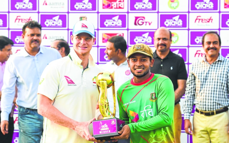Australian cricket captain Steven Smith (L) and Bangladeshi cricket captain Mushfiqur Rahim (R) hold the tournament trophy during the presentation ceremony following the second cricket Test between Bangladesh and Australia at Zahur Ahmed Chowdhury Stadium in Chittagong on September 7, 2017. / AFP PHOTO / Munir UZ ZAMAN