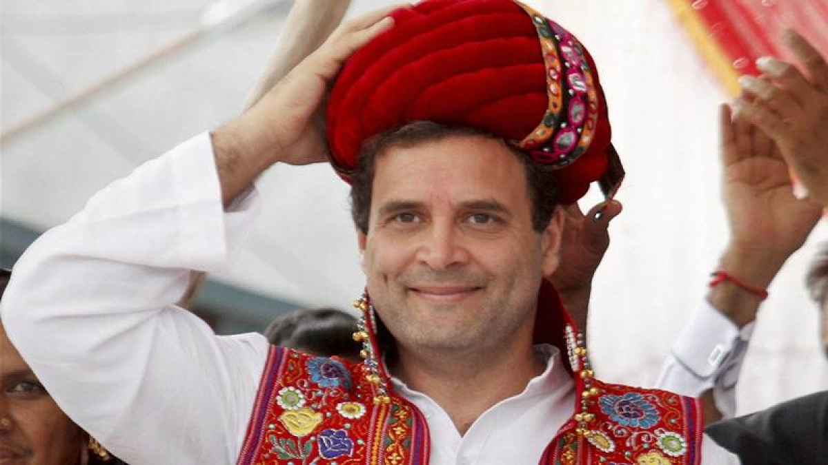 Jamnagar: Rahul Gandhi wears a turban presented to him by his supporters, at a public meeting in Jamnagar, Gujarat on Tuesday. PTI Photo