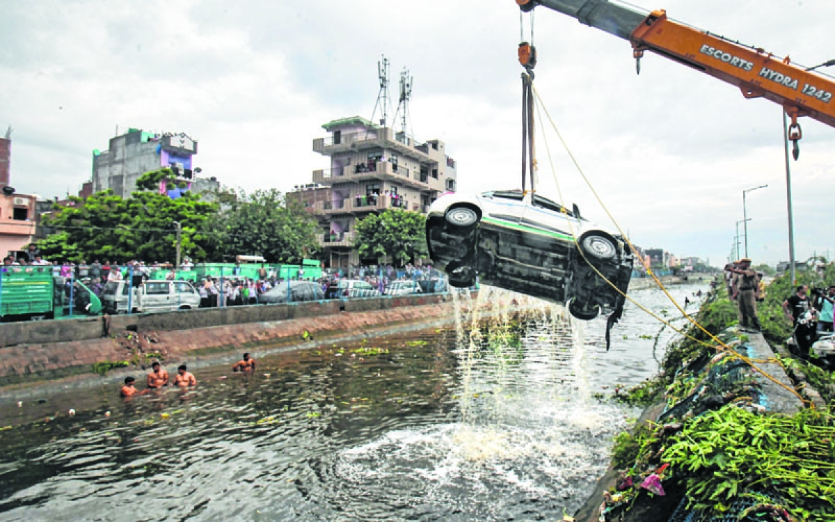 New Delhi: A car being pulled out of a canal as the rescue operations are underway after a part of the Ghazipur garbage landfill collapsed in east Delhi on Friday afternoon. Several people and a vehicle were swept into the canal after the mishap. PTI Photo    (PTI9_1_2017_000128B)
