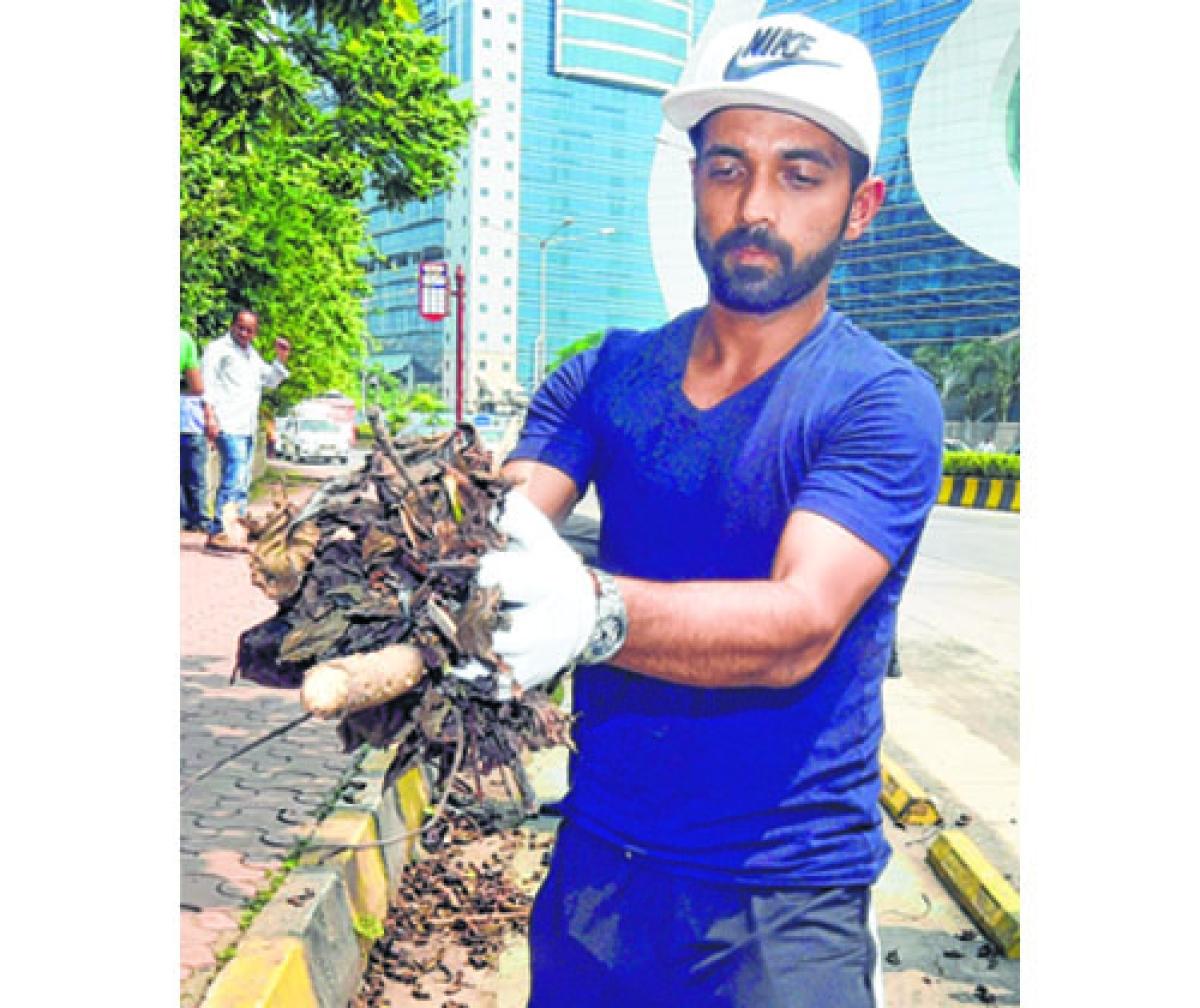 Mumbai: Cricketer Ajinkya Rahane takes part in a cleanliness drive as part of the Swachhata Hi Seva campaign in Mumbai on Monday. PTI Photo by Shashank Parade  (PTI10_2_2017_000091B)