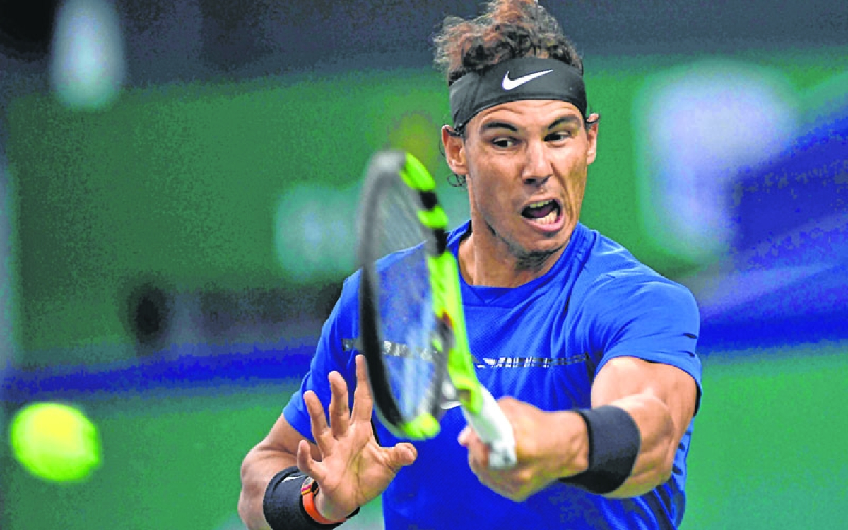 Rafael Nadal of Spain hits a return during his men's third round singles match against Fabio Fognini of Italy at the Shanghai Masters tennis tournament in Shanghai on October 12, 2017. / AFP PHOTO / NICOLAS ASFOURI