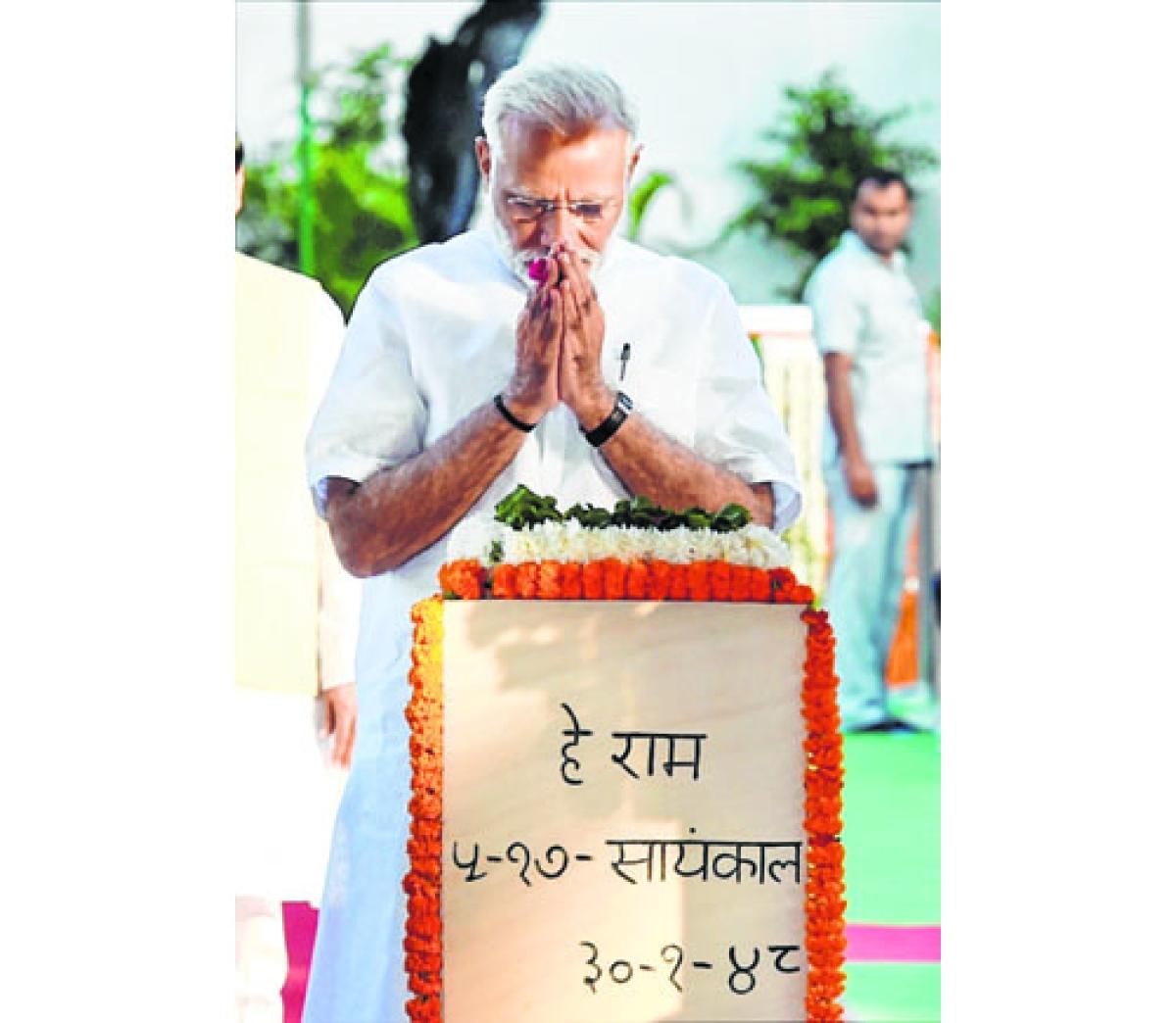 New Delhi:  Prime Minister Narendra Modi paying tribute at Mahatma Gandhi's memorial on his 148th birth anniversary at Gandhi Smriti in New Delhi on Monday. PTI Photo by Kamal Singh(PTI10_2_2017_000167B)
