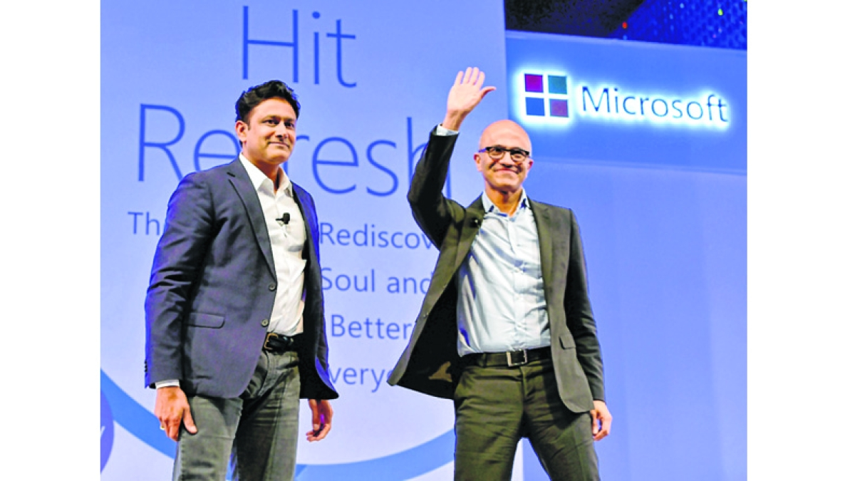 Microsoft CEO Satya Nadella waves as former Indian cricket team captain Anil Kumble looks on, during an event in New Delhi.