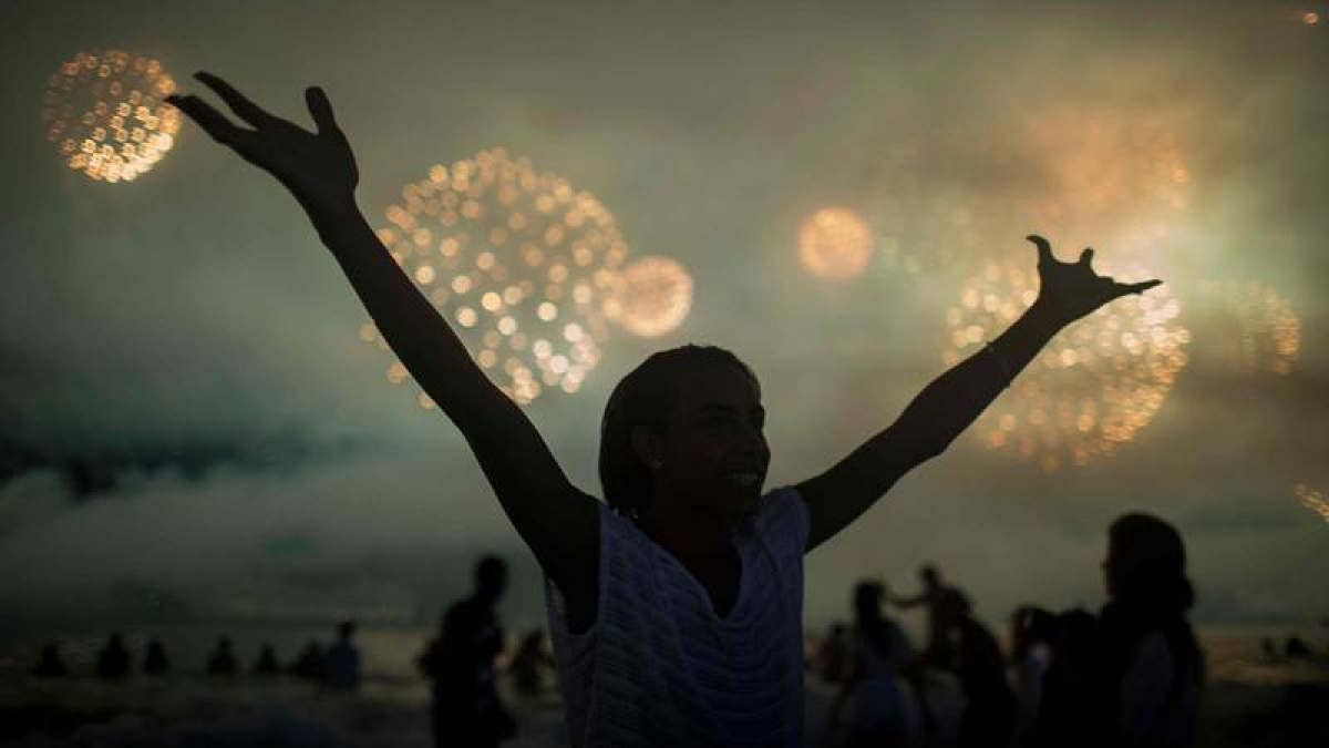 People watch fireworks during New Year's celebrations at Copacabana beach in Rio de Janeiro on January 1, 2018. / AFP PHOTO / MAURO PIMENTEL