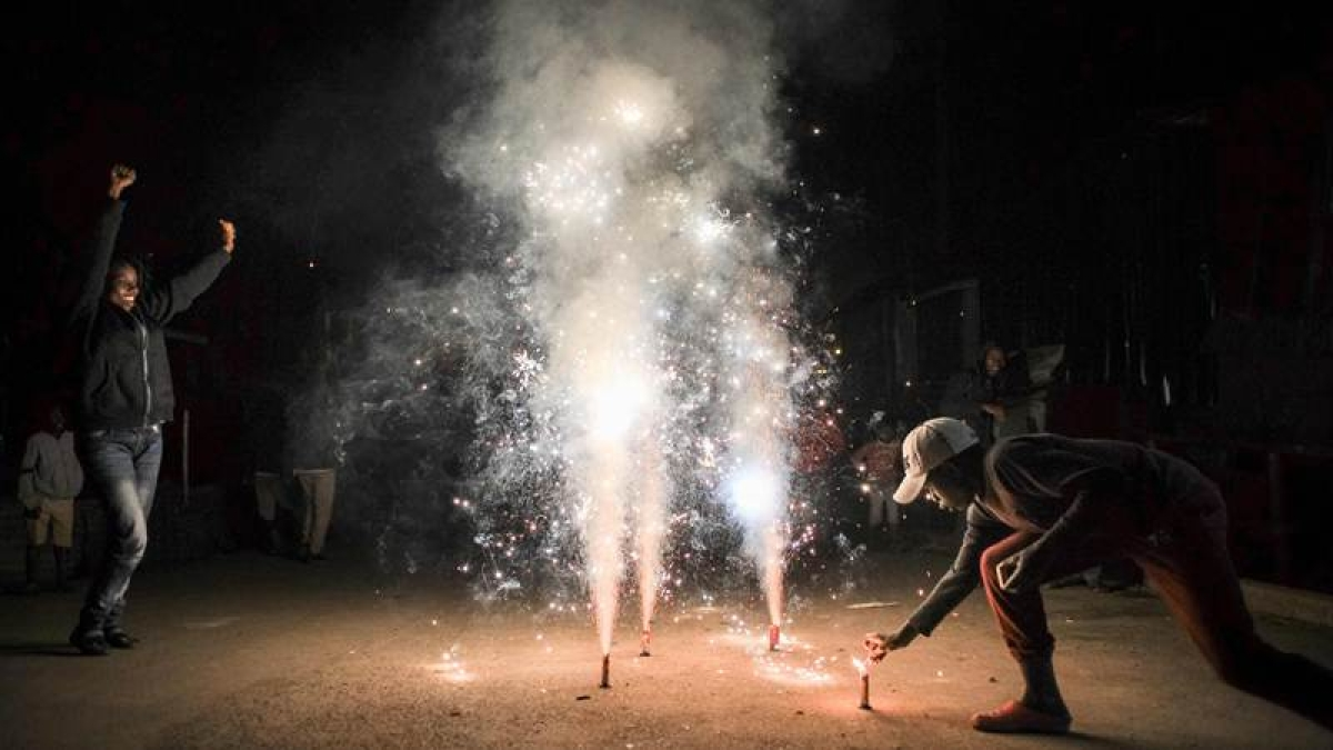 People light fireworks on a street to celebrate New Year's on January 1, 2018, at Kibera slum in Nairobi, Kenya, / AFP PHOTO / Brian Otieno