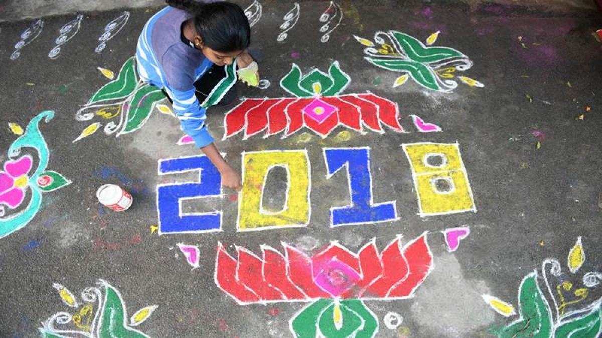 """A woman applies coloured powder to a """"rangoli"""", a Hindu ritual design, to usher in the New Year in front of a home in Hyderabad on January 1, 2018. / AFP PHOTO / Noah SEELAM"""