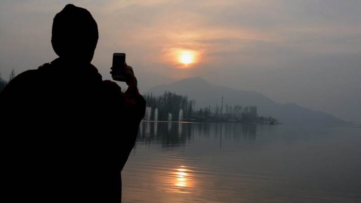 A youth uses his mobile phone to capture the pictures of last sunset of year-2017, at Dal Lake in Srinagar on Sunday. PTI Photo