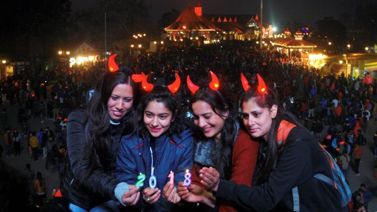 Shimla: Girls hold candles of 2018 to welcome the New Year at Ridge in Shimla. PTI Photo