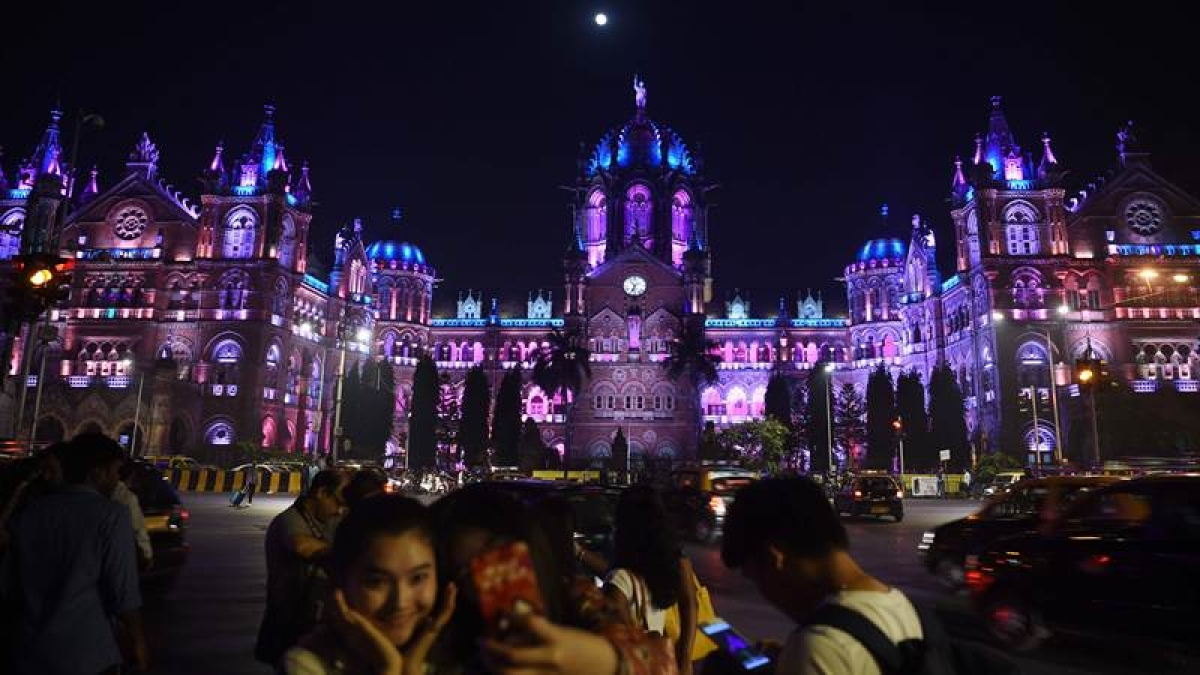 Indians take pictures in front of the lit up Chattrapathi Shivaji Terminus (CST) railway station ahead of New Year's eve. / AFP PHOTO / PUNIT PARANJPE