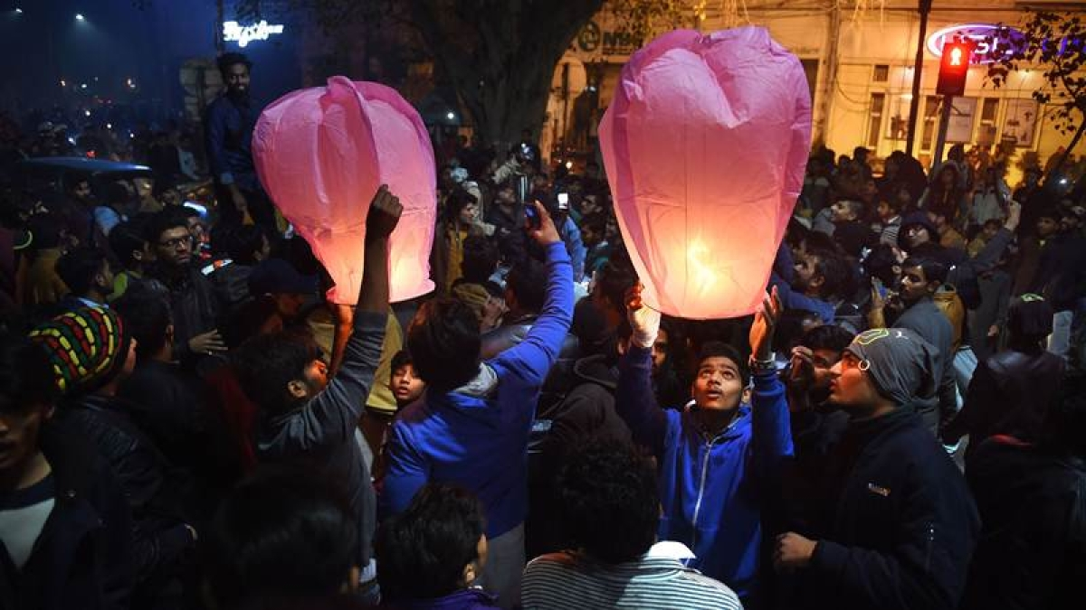 Pakistani people prepare to release lanterns as they gather to celebrate the new year in Lahore early on January 1, 2018. / AFP PHOTO / ARIF ALI