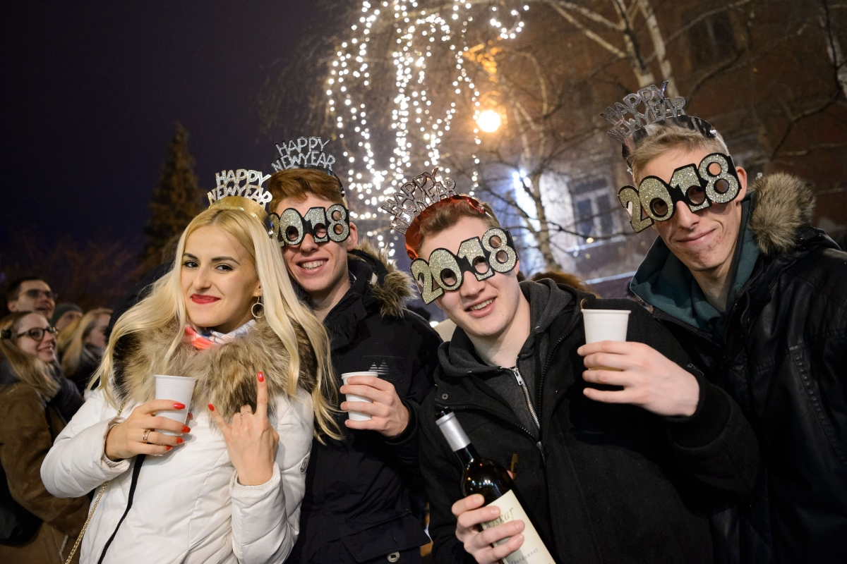 People celebrate during New Year's celebrations just after midnight in Ljubljana, Slovenia on January 1, 2018. / AFP PHOTO / Jure Makovec