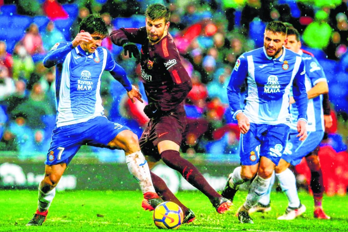 Barcelona's Spanish defender Gerard Pique (C) vies with Espanyol's Spanish forward Gerard Moreno (L) during the Spanish league football match between RCD Espanyol and FC Barcelona at the RCDE Stadium in Cornella de Llobregat on February 4, 2018. / AFP PHOTO / PAU BARRENA